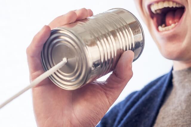 糸電話に向けて喋っている人